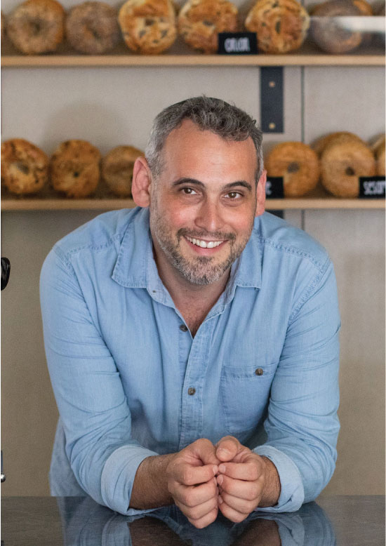 This is an image of Barry, owner of The Bagel Co in serving bagels and coffee inRose Bay and Surry Hills.